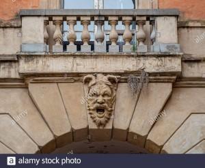 facciata-in-pietra-scolpita-del-diavolo-su-un-arco-di-via-zamboni-che-conduce-alla-zona-ebraica-di-bologna-italia-2c6g246